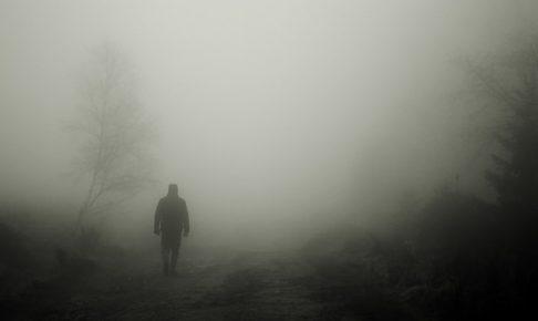 不安げな霧の中を歩く人